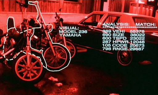 A screenshot from the terminator movie, when the T-800 recognizes a motor cycle. The image is red with white contours around the motor cycle and white text
